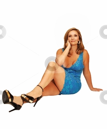 Young woman sitting on the floor. stock photo, An friendly blond girl in a blue dress sitting on the floor for white background. by Horst Petzold
