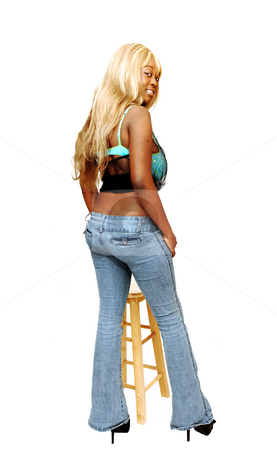 Young Jamaican girl standing. stock photo, An busty young Jamaican girl in jeans whit long blond hair and high heels standing in a studio for white background. by Horst Petzold