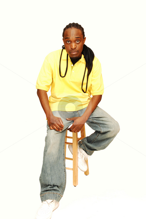 Young African American man. stock photo, Young African American sitting on an bar chair in the studio for white background. by Horst Petzold