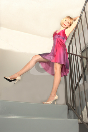 Young woman standing. stock photo, An friendly blond girl in a colorful dress is standing in the sterway of an high rise and an joying her self. by Horst Petzold