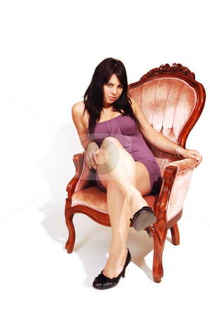 Young woman sitting in armchair. stock photo, An friendly girl in an short pink dress sitting in an armchair in a studio