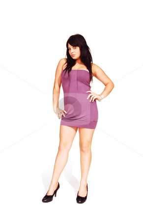 Standing woman in pink dress.  stock photo, An friendly girl in an short pink dress standing in an studio  for white background. by Horst Petzold