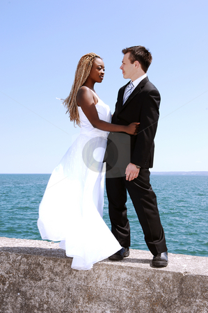 Young married couple. stock photo, An young married couple on a photo shoot at the Hamilton harbor standing on a concrete wall with the lake Ontario in the background. by Horst Petzold