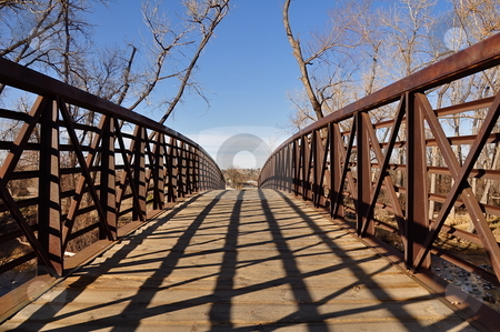 Old Metal Footbridge stock photo, An old metal bridge stands under a blue Colorado sky in the winter with trees in the background.  There is space for copy. by Ben O'Neal