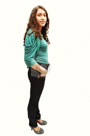 Young smiling girl. stock photo, A young girl in jeans and turquoise sweater standing for white background. by Horst Petzold