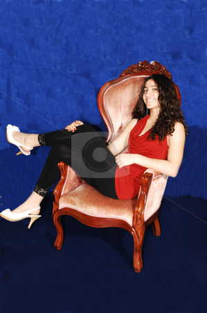 Young Lady in armchair. stock photo, A young girl in black tights and red sweater sitting in an arm chair and her long dark hair is hanging down. by Horst Petzold