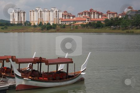 Tourist boat parking stock photo, Scenic view of tourist boat in the lake at foreground and apartments across as a background by Purtojo Soejarno