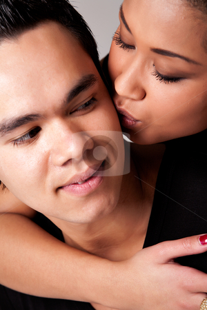 Gently kissing my Indonesian lover on his cheek stock photo, Portrait of Indonesian boy- and girlfriend in love by Frenk and Danielle Kaufmann
