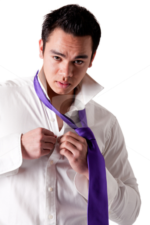 Portrait of a strong young indonesian clothing himself stock photo, Business portrait of a strong indonesian man by Frenk and Danielle Kaufmann