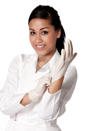 Portrait of a beautifull Indonesian nurse putting gloves on stock photo, Beautifull Indonesian nurse in white uniform by Frenk and Danielle Kaufmann