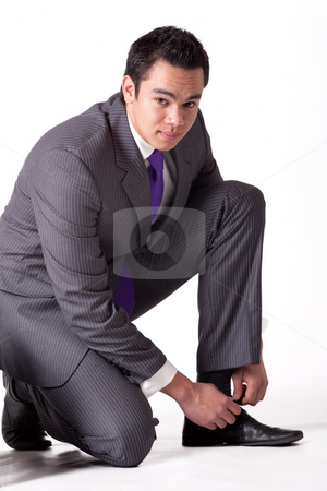 Strong young indonesian man in a suit tying his shoes stock photo, Business portrait of a strong indonesian man by Frenk and Danielle Kaufmann