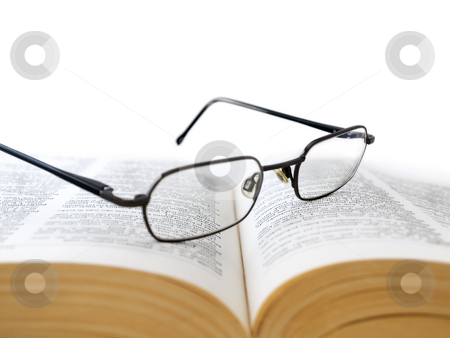 Opened book with glasses stock photo, Closeup of opened book with glasses on it, on white background,shallow DOF,focus on glasses by Vladimir Koletic