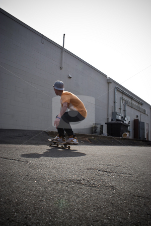 Skateboarding Around stock photo, A young man skateboarding in an urban area. by Todd Arena