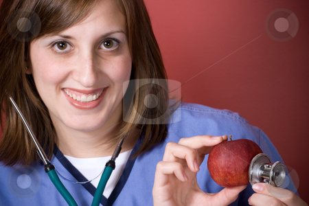 Healthy Diet stock photo, A young nurse is holding her stethoscope onto a red apple.  An apple a day keeps the doctor away. by Todd Arena