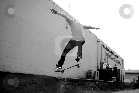 Skateboarder stock photo, A young skateboarder doing a stunt in an urban area. by Todd Arena