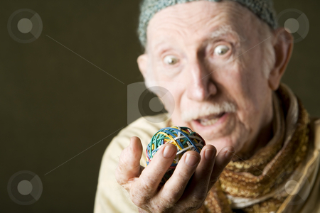 Man contemplating a rubber band ball stock photo, Senior man in knit cap contemplating a colorful rubber band ball by Scott Griessel