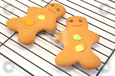 Two Gingerbread Men on a Cooling Rack stock photo, Focus is on the face of the right hand man by Helen Shorey