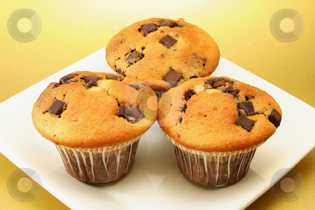 Three choc chip muffins  stock photo, Three delicious choc chip muffins on a square plate with a golden background by Helen Shorey