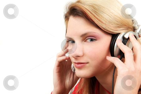 Headphones stock photo, Young woman is listening to the music with headphones by Tom P.