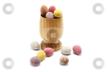 Easter Eggcup stock photo, Small wooden eggcup with candy coated chocolate easter eggs by Helen Shorey