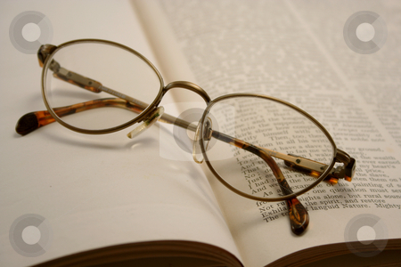Reading Glasses on an Old Book stock photo, Pair of reading glasses on an old book, some text is legible by Helen Shorey