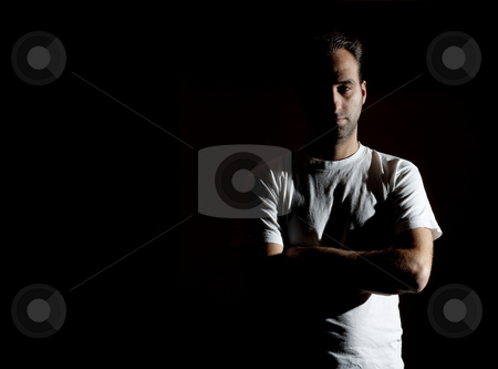 Rude mistery man stock photo, Dark image of a no shaved dangerous looking guy in a rude pose by Ivan Montero