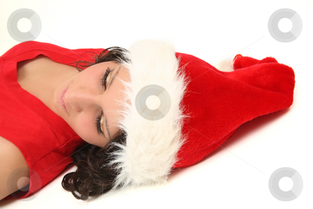 Girl in Santa's cap stock photo, Young teenage girl is having rest in santa's cap by Tom P.