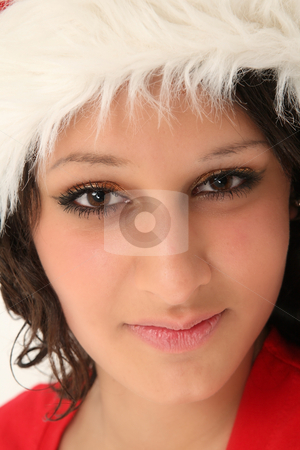 Girl in Santa's cap stock photo, Teenage girl closeup face in santa's cap by Tom P.