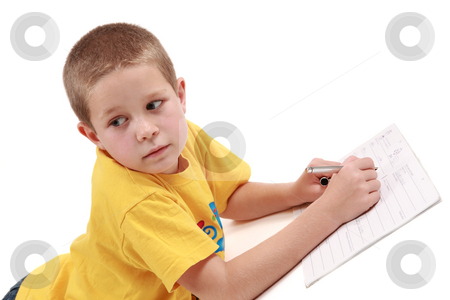 Young boy  stock photo, Young boy is writting in his exercise book with pen by Tom P.
