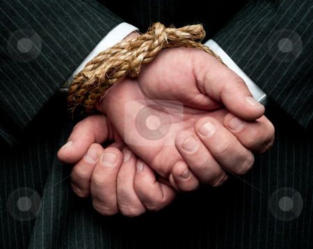 A horizontal view of a business man with his hands tied behind h stock photo, A horizontal view of a business man with his hands tied behind him. Concept: