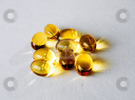 Cod liver oil stock photo, Gold capsules of cod liver oil on background by Leyla Akhundova