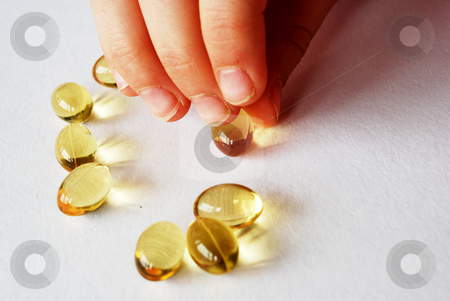 Cod liver oil  stock photo, Capsule in kid's finger for nails treatment by Leyla Akhundova