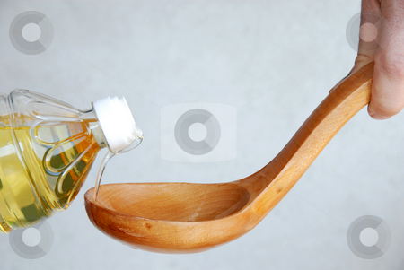 Pouring oil in wooden spoon stock photo, Pouring vegetable oil in large wooden spoon by Julija Sapic