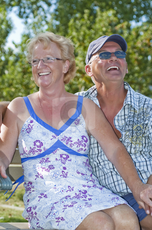 Aged Couple stock photo, Aged couple sitting on a bench and laughing out loud by Vlad Podkhlebnik