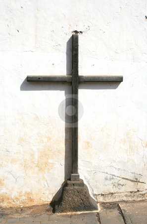 Simple Wooden Cross stock photo, A simple wooden cross mounted on a shaped piece of volcanic rock against a whitewashed wall. by Helen Shorey