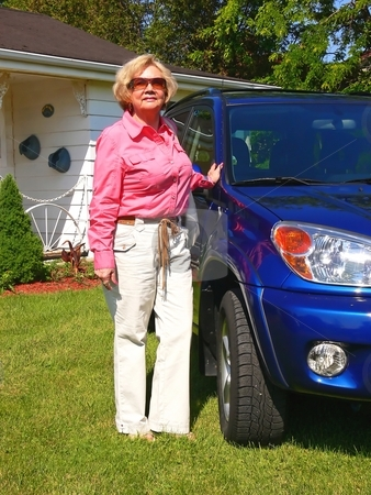 Lady with blue car                             stock photo, An senior citizen with her new blue SUV on the front lawn of her house. by Horst Petzold