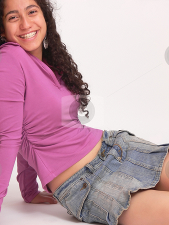 Happy young girl     stock photo, An beautiful young girl in an denim mini skirt is sitting on the floor and her long dark curly hair hanging down on white background. by Horst Petzold