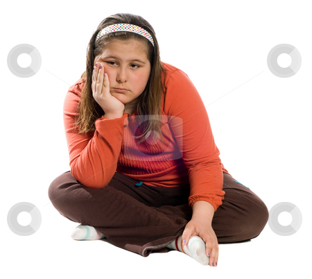 Boredom stock photo, A young girl sitting on the floor crosslegged and looking bored, isolated against a white background by Richard Nelson