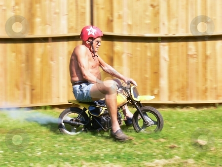 Grandpa on a minibike  stock photo, Grandpa in racing on an minibike in his backyard. by Horst Petzold