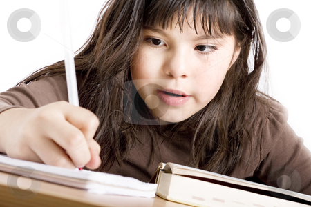 Cute girl doing homework stock photo, Mixed race girl doing homework over white background by iodrakon