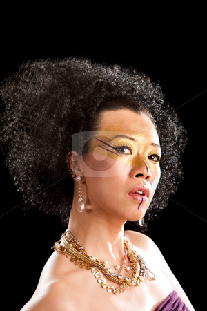 Tribal Queen stock photo, Beautiful face of an Asian woman with black curly fro hair, gold with purple makeup, bare shoulders and luxury necklace, isolated by Paul Hakimata