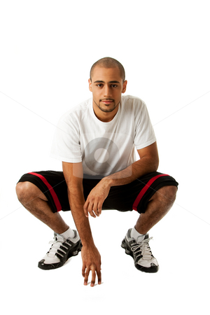 Crouching Sporty guy stock photo, Sporty handsome African Hispanic guy crouching and hand on floor, isolated by Paul Hakimata