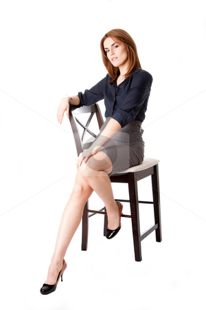 Beautiful business woman stock photo, Beautiful brunette business woman sitting wearing gray skirt and blue blouse with hand on leg, isolated by Paul Hakimata