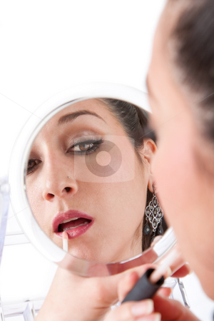Woman applying makeup stock photo, Beautiful caucasian woman applying makeup lipstick on lip while looking in hand held mirror, isolated by Paul Hakimata