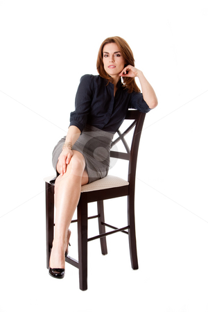 Beautiful business woman stock photo, Beautiful brunette business woman sitting wearing gray skirt and blue blouse with hand on leg with legs crossed, isolated by Paul Hakimata