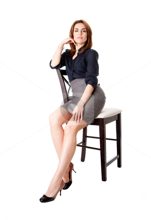 Beautiful business woman stock photo, Beautiful sexy brunette business woman sitting wearing gray skirt and blue blouse with hand on leg, isolated by Paul Hakimata