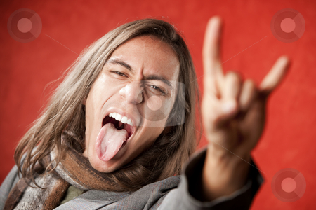 Handsome Young Man Making a Hand Gesture stock photo, Closeup Portrait of Handsome Young Man with Long Hair Making Hand gesture and Sticking Out Tongue by Scott Griessel