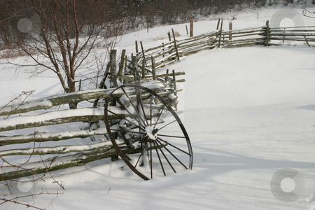 Winter Wheel II stock photo, An old iron wagon wheel leaning against a wood split-rail fence, covered in snow. by Rick Parsons