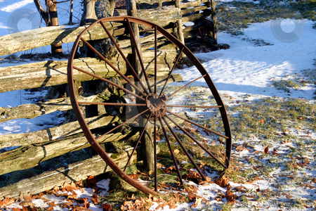 Rusty Wheel stock photo, Old rusty iron wheel leaning against a wood split-rail fence, winter scene, not much snow. by Rick Parsons