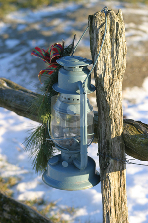 Christmas Lamp II stock photo, An old oil lamp hanging from a wood fence post, some snow in the background. by Rick Parsons
